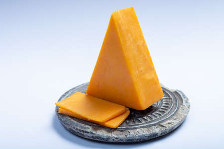 Piece of hard orange Cheddar cheese on grey stone plate isolated, close up