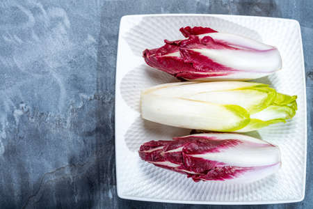 Fond de nourriture, concept plat avec endive ou chicorée belge verte fraîche et légumes Radicchio rouges, également connus sous le nom de salade witlof Banque d'images