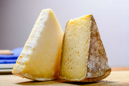 Pieces of French Tomme and Cantal cheese, close-up Stock fotó