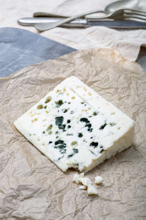 Piece of French blue cheese Roquefort, made from sheep milk in caves of Roquefort-sur-Soulzon Foto de archivo - 115735259