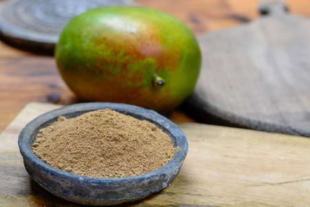 Amchoor or aamchur, mango powder, fruity spice powder made from dried unripe green mangoes in India, used to flavor foods close-up Banco de Imagens