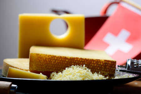 Assortment of Swiss cheeses Emmental or Emmentaler medium-hard cheese with round holes, Gruyere, appenzeller and raclette used for traditional cheese fondue and gratin and flag of Switzerland 免版税图像