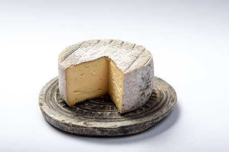 Round mature French Tomme cheese with one cutted piece on grey stone plate isolated close up