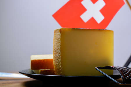 Block of Swiss hard cheese appenzeller used for traditional fondue and gratin and flag of Switzerland close-up