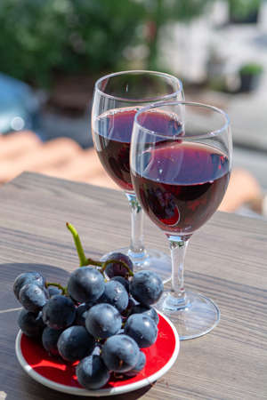 Two wine glasses with red wine served with red grape on outdoor terrace in sunny summer day