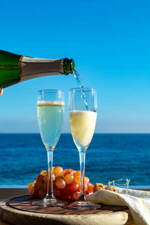 Waiter pouring Champagne, prosecco or cava in two glasses on outside terrace with sea view  close up Stock Photo