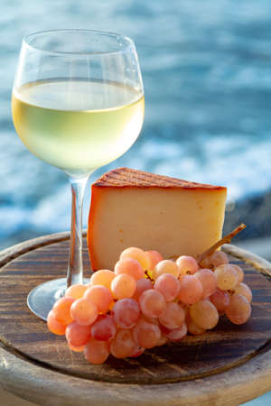 Spanish goat milk cheese with paprika coating and ripe pink table grapes served with white wine on outdoor terrace close up Stock fotó