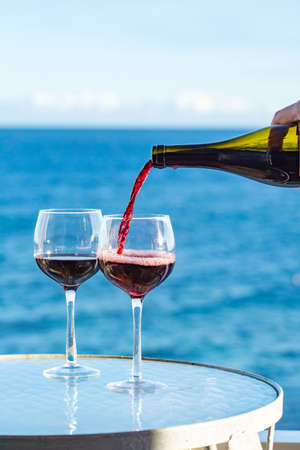 Waiter pouring aperitif red wine in glasses on outdoor tessace witn sea view in sunny day
