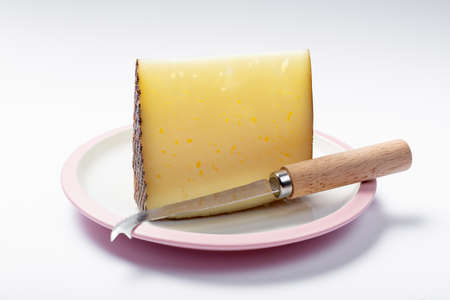 Piece of Spanish hard scheep milk cheese Manchego on white board, close up isolated