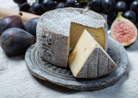 Round mature French Tomme cheese with one cutted piece served with black grape and fresh ripe figs close up