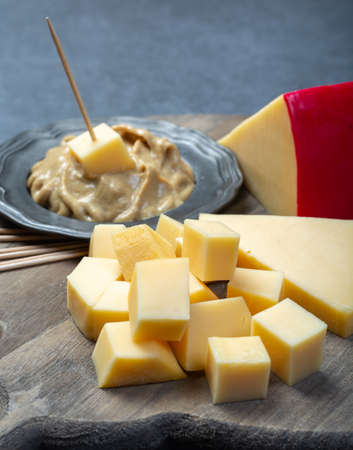Snack food, blocks of Dutch red ball Edam cheese and mustard