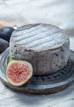 Whole round mature French Tomme cheese served with black grape and fresh ripe figs close up