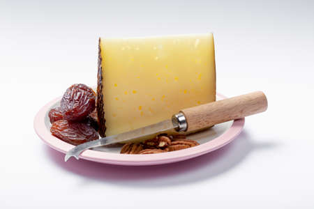 Piece of Spanish hard scheep milk cheese Manchego on white board served with fresh ripe figs and cheese knife, close up isolated