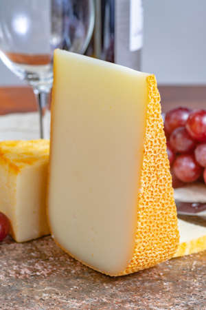 Pieces of french yellow cheeses, Pur Brebis sheep melk cheese fron Pyrenees and Saint Paulin creamy, mild, semi-soft French cheese from pasteurized cow milk Standard-Bild - 118653687