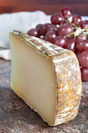 Piece of tasty Ossau-Iraty or Esquirrou sheep cheese produced in south-western France, Northern Basque Country Imagens