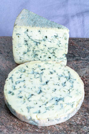 Pieces of Fourme Ambert and Blue Auvergne semi-hard AOP French blue cheeses made from raw cow milk in Auvergne, France