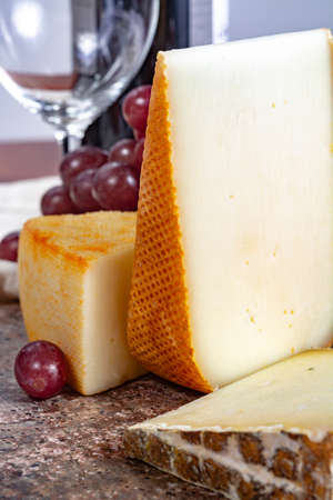 Marble plate with sheep milk cheeses Pur Brebis and Ossau-Iraty from Pyrenees and yellow Saint Paulin cow milk cheese, France cheeses served as dessert with grapes close up Standard-Bild - 118681707