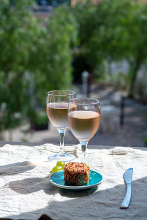 Rose wine of Provence, France, served cold with soft goat cheese on outdoor terrace in two wine glasses in sunny day