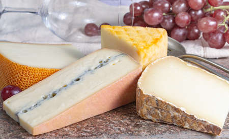 Marble plate with sheep milk cheeses Pur Brebis and Ossau-Iraty from Pyrenees, yellow Saint Paulin and Morbier cow milk cheeses, France cheeses served as dessert with grapes close up
