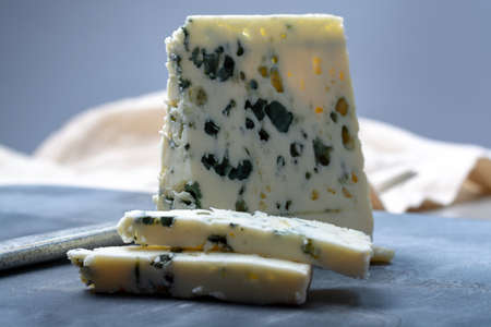 Piece of French blue cheese Roquefort, made from sheep milk in caves of Roquefort-sur-Soulzon Foto de archivo - 118725699