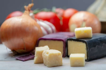 Mini black and dark red waxed cheddar cheeses with strong flavor made from West Country milk and and age-old methods with onion and garlic in England close up