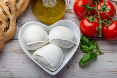 Love mozzerella, balls of buffalo mozzarella, soft Italian scheese made from the milk of Italian Mediterranean buffalo in heart shaped plate close up