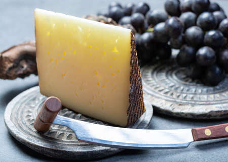 Piece of Spanish hard scheep milk cheese Manchego served with black grapes close up
