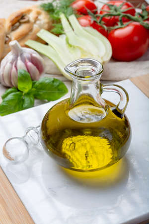 Virgin natural olive oil is glass bottle, served with traditional Mediterranean food, fresh tomatoes, olive bread, basil, fennel Stok Fotoğraf