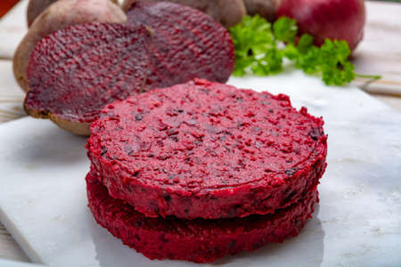 Healthy vegetarian food, raw round burgers made from red beetroot close up, good for vegans Stockfoto