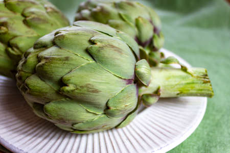 Heads of green fresh uncooked artichoke flowers close up