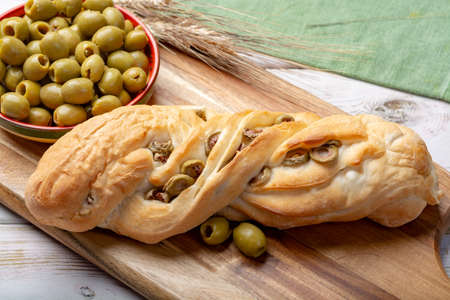 Fresh baked white wheat bread bun with green olives close up