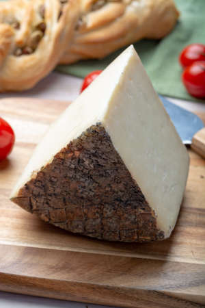Italian cheese, piece of mature Tuscan Pecorino sheep cheese served with olive bread and tomatoes close up