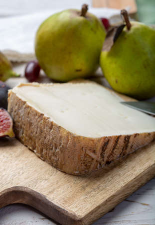Piece of French cheese Tomme de Brebis made from sheep milk served as dessert with fresh figs and pears close up