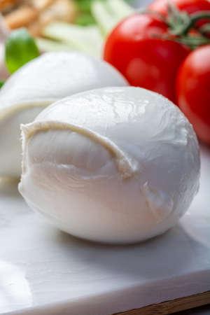 Balls of buffalo mozzarella, soft Italian scheese made from the milk of Italian Mediterranean buffalo close up Фото со стока