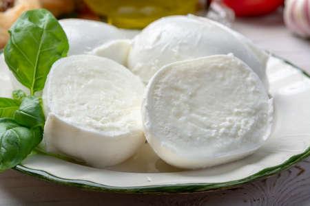 Balls and pieces of buffalo mozzarella, soft Italian scheese made from the milk of Italian Mediterranean buffalo close up