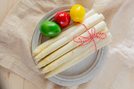 New harvest of white asparagus and colored Easter eggs, high quality raw asparagus in spring season, ingredients for Easter dinner close up 免版税图像