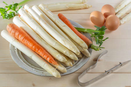 New harvest of white asparagus, high quality raw asparagus, carrot and selery on board in spring season, ready to cook close up