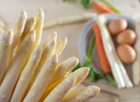 New harvest of white asparagus, high quality raw asparagus, carrot and selery in spring season, ready to cook close up