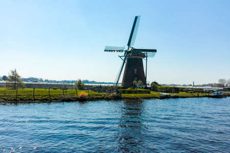 Waterways and canals in North Holland with boats and view on traditional Dutch mill, spring landscape Stock Photo