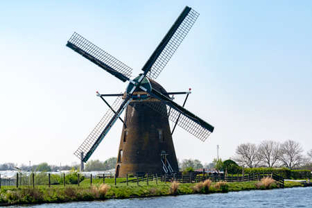 Traditional Dutch wind mill built along canal in North Holland, spring landscape
