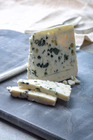 Piece of French blue cheese Roquefort, made from sheep milk in caves of Roquefort-sur-Soulzon Foto de archivo - 121424160