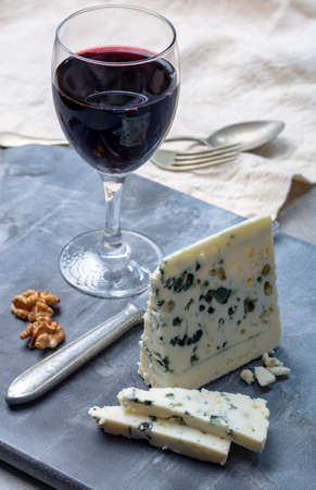 Piece of French blue cheese Roquefort, made from sheep milk in caves of Roquefort-sur-Soulzon and glas with red wine 免版税图像
