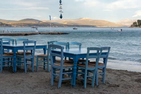 Traditional greek tavern with wooden tables on sandy beach near water waiting for tourists in Tolo, Peloponnese, Greece, vacation season is starting Foto de archivo