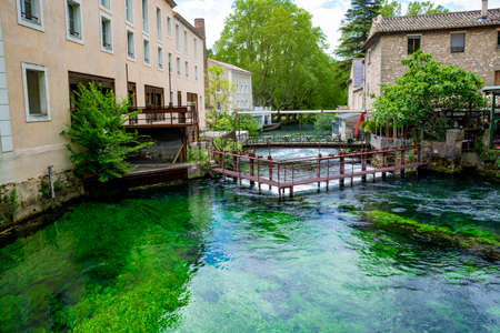 South of France, view on small touristic Provencal town of poet Petrarch Fontaine-de-vaucluse with emerald green waters of Sorgue river