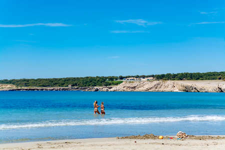 Crystal clear blue water of  Mediterranean sea on St.Croix Martigues white sandy and two undefinad women, Provence, France, vacation destination Stock Photo