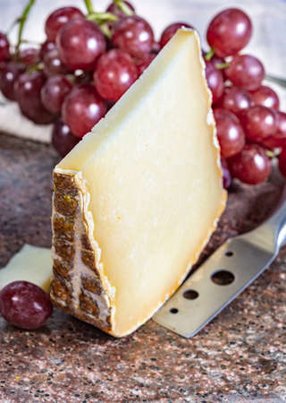 Piece of tasty Ossau-Iraty or Esquirrou sheep cheese produced in south-western France, Northern Basque Country Banque d'images