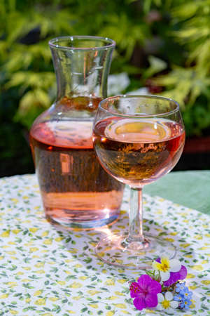 Wine carafe and glass with cold rose wine and wild flowers in summer sunny day in garden