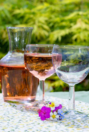 Wine carafe and glasses with cold rose wine and wild flowers in summer sunny day in garden