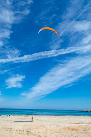 Watersport on vacation, kitesurfer is ready for action on sandy beach with blue sea water in sunny day