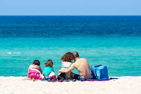 unidentified family with two children sitting back on white sandy beach and looking at crystal clear blue sea water.